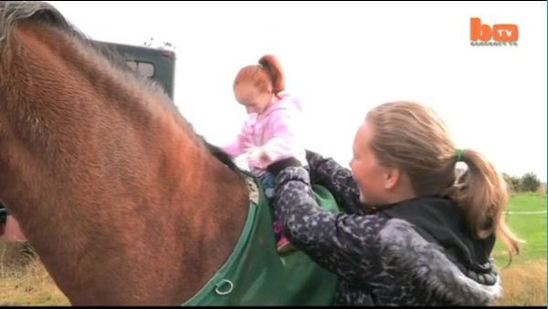 The world's smallest girl Charlotte Garside rides a horse. (Screen grab Daily Mail)