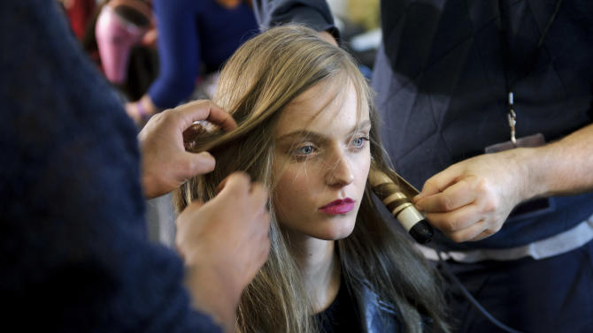 A model is prepared ahead of the Paul Smith collection during London Fashion Week, Sunday, Feb. 17, 2013, London. (Photo by Jonathan Short/Invision/AP)