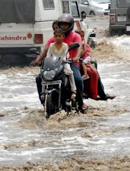 <p>A motor-cyclist and his passengers travel along a water-logged road in Jalandhar on Saturday. Assam state has been hardest hit by the annual rains with the mighty Brahmaputra river overflowing its banks, while flooding has also struck the surrounding states of Arunachal Pradesh, Manipur and Meghalaya.</p>