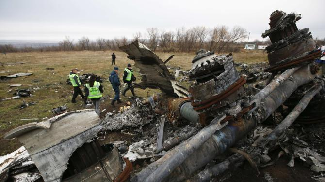 Dutch investigators and an Emergencies Ministry member work at the site where the downed Malaysia Airlines flight MH17 crashed, near the village of Hrabove in Donetsk region