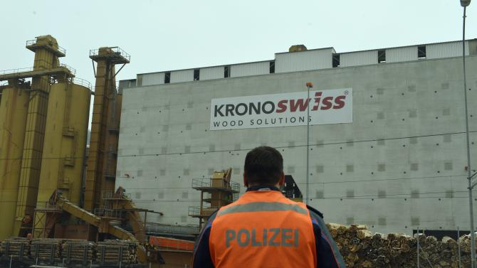 """A police stands in front of a wood-processing company in Menznau, central Switzerland, Wednesday, Feb. 27, 2013, where several people were killed in a shooting. Police in Lucerne canton (state) said in a statement that the shooting occurred shortly after 9 a.m. at the premises of Kronospan, a company in the small town west of Lucerne. They said there were """"several dead and several seriously injured people"""" and that rescue services were deployed and the scene sealed off. (AP Photo/Keystone, Urs Flueeler)"""