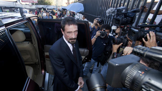 "Software company founder John McAfee poses for pictures after a press conference outside the Supreme Court in Guatemala City, Tuesday, Dec. 4, 2012. A Guatemalan official says McAfee, who has been identified as a ""person of interest"" in the killing of his neighbor in Belize, 52-year-old Gregory Faull, was arrested on Wednesday, Dec. 5, 2012 in Guatemala City for entering the country illegally. (AP Photo/Moises Castillo)"