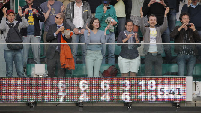 Spectators applauds after the second round match opposing France's Paul-Henri Mathieu to USA's John Isner during their second round match in the French Open tennis tournament at the Roland Garros stadium in Paris, Thursday, May 31, 2012. Mathieu won 6-7, 6-4,6-4, 3-6, 18-16. Electronic score board shows the total match time. (AP Photo/Christophe Ena)