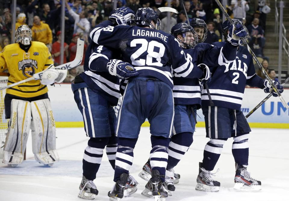 CORRECTS TO SECOND PERIOD- Yale's Clinton Bourbonais, second from right, celebrates after his goal past Quinnipiac goalie Eric Hartzell, left, during the second period of the NCAA men's college hockey Frozen Four national championship game in Pittsburgh, Saturday, April 13, 2013. (AP Photo/Gene Puskar)
