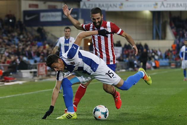 Atletico's Arda Turan from Turkey, right, in action with Espanyol's Hector Moreno, left, during a Spanish La Liga soccer match between Atletico Madrid and Espanyol at the Vicente Calderon stad