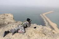 FILE - In this Friday, Dec. 30, 2011 file photo, a member of the Iranian military takes position in a drill on the shore of the sea of Oman, on Friday, Dec. 30, 2011. For leaders on the Iranian side of the Gulf, the past days have offered some hard lessons in the politics of oil. Iran has watched as the leader of its most influential ally, China, began a tour of Gulf Arab states and other Asian envoys held talks with oil-rich Gulf rulers, who have shown growing confidence to stand up against rival Iran and use tougher tactics to try to gain the upper hand in their standoffs with the Islamic Republic. (AP Photo/YJC, Mohammad Ali Marizad, File)