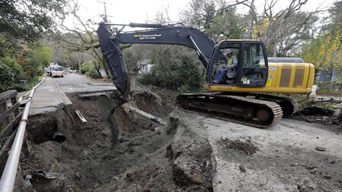 A worker from Pacific General Engineering works to clear the damage on the road caused by overflow water from Lafayette Creek in Lafayette, Calif., Tuesday, Dec. 4, 2012. Just as Northern California residents recovered from a series of wet, windy storms, another system on the way is expected to drench the area. (AP Photo/Marcio Jose Sanchez)