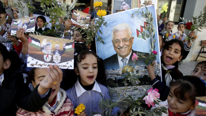 Palestinian schoolgirls hold pictures of President Mahmoud Abbas with Yasser Arafat, flowers and olive branches during a rally supporting the Palestinian UN bid for observer state status, in the West Bank city of Nablus, Wednesday, Nov. 28, 2012. The Palestinians will request to upgrade their status on November 29. The status could add weight to Palestinian claims for a state in the West Bank, Gaza Strip and east Jerusalem, territories captured by Israel in the 1967 Mideast war from Jordan. (AP Photo/Nasser Ishtayeh)