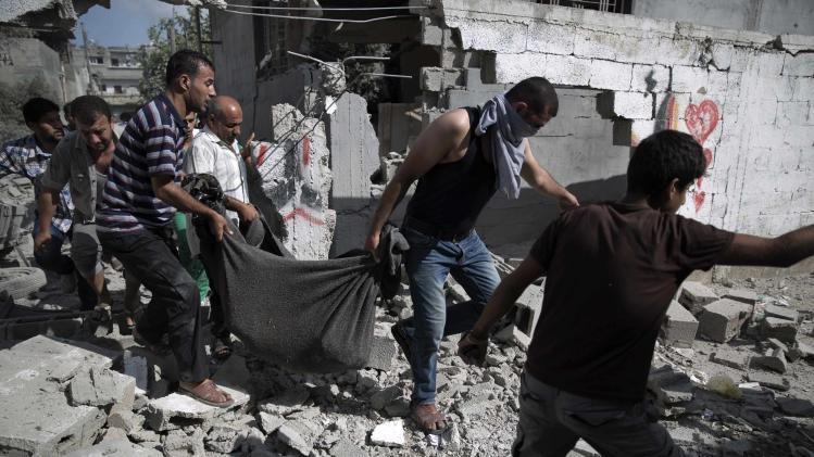 Palestinians carry a body from a destroyed building in Beit Hanoun town in the northern Gaza Strip