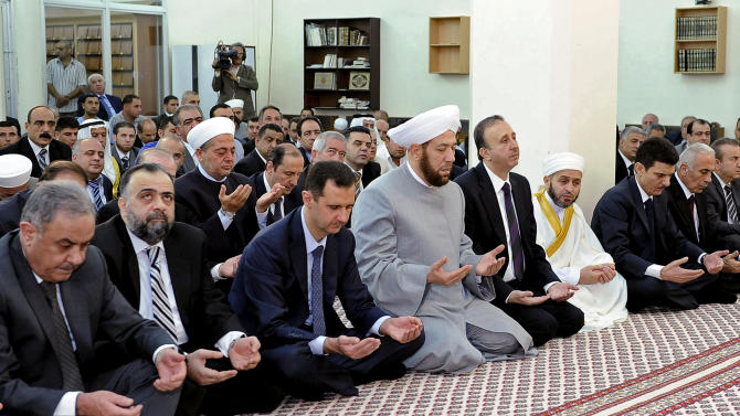 In this photo released by the Syrian official news agency SANA, Syrian president, Bashar Assad, performs Eid prayers in the Hamad Mosque in Damascus, Syria, Sunday, Aug. 19, 2012. Assad prayed early on Sunday at the start of Eid al-Fitr, a three-day holiday marking the end of the holy month of Ramadan. The last time he appeared in public was on Wednesday, July 4, 2012 when he gave a speech in parliament. (AP Photo/SANA)