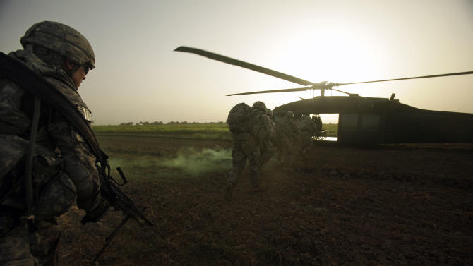 U.S. Army Pvt. 1st Class David Hedge from Bealeton, Va., left, and fellow soldiers from 1st Battalion, 18th Infantry Regiment rush to a Blackhawk helicopter after a an operation to disrupt weapons smuggling in Istaqlal, north of Baghdad, Iraq, Monday, Aug. 8, 2011. (AP Photo/Maya Alleruzzo)