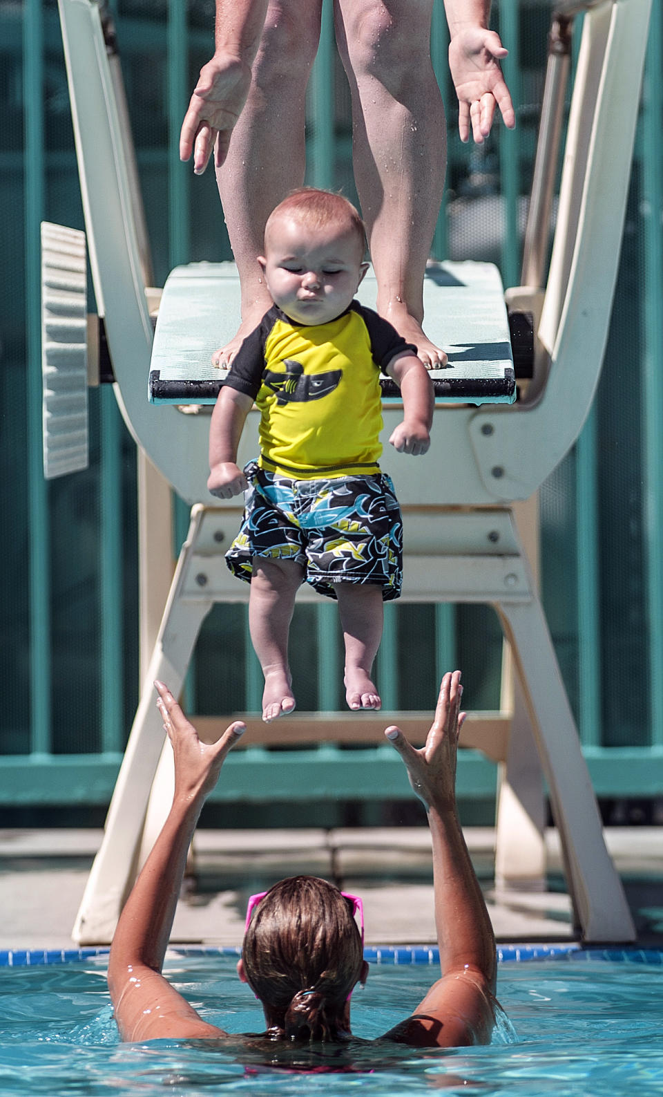 "Matthew Dayton, 6 months, is dropped into the pool by his mother Stephanie Dayton into the arms of lifeguard/swim instructor Nicolette Conrad during a ""Mommy and Me"" swim class at the Brea Plunge on Thursday, June 27, 2013, in Brea, Calif. (AP Photo/The Orange County Register, Bruce Chambers)"