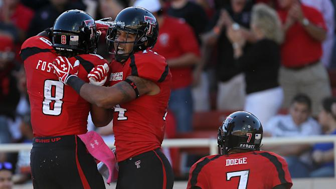Texas Tech's SaDale Foster (8), Darrin Moore (14) and Seth Doege celebrate a touchdown against West Virginia during an NCAA college football game in Lubbock, Texas, Saturday, Oct. 13, 2012. (AP Photo/Lubbock Avalanche-Journal, Stephen Spillman) LOCAL TV OUT