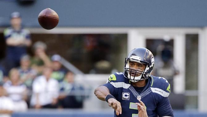 Seattle Seahawks quarterback Russell Wilson passes against the Denver Broncos in overtime in an NFL football game, Sunday, Sept. 21, 2014, in Seattle. The Seahawks won 26-20