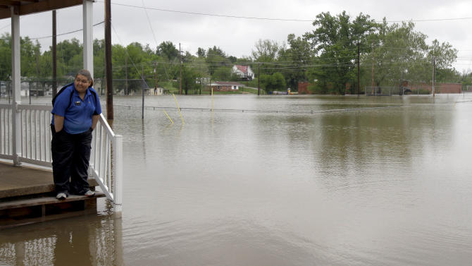 Erica Cross stands on a friend's porch surrounded by floodwater Tuesday, April 26, 2011, in Poplar Bluff, Mo. Powerful storms that swept through the nation's midsection have pushed river levels to dangerous heights and are threatening to flood several towns in Missouri. (AP Photo/Jeff Roberson)