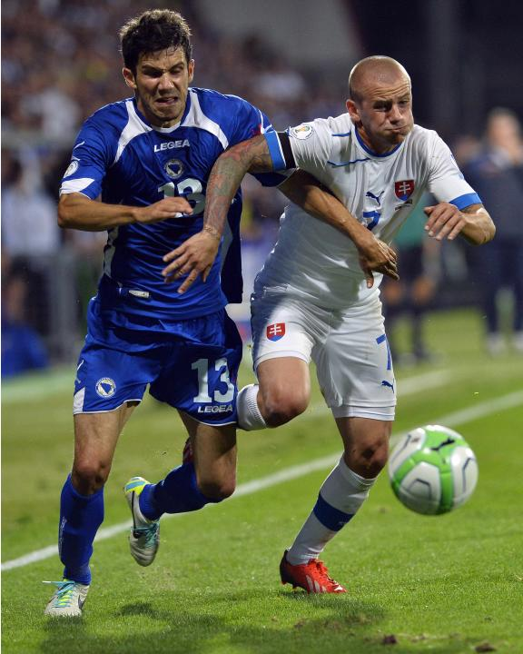 Slovakia's Vladimir Weiss fights for the ball with Bosnia's Mensur Mujdza during their 2014 World Cup qualifying soccer match in Zilina