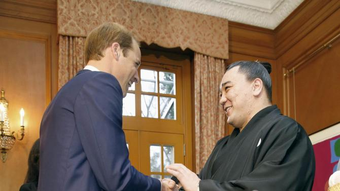 Britain's Prince William, Duke of Cambridge, greets Mongolian-born sumo wrestler Yokozuna or grand champion Harumafuji during a reception at the British Ambassador's official residence in Tokyo