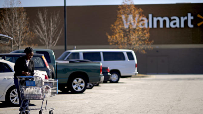 A shopper loads bags into a car in the parking lot of the Walmart Monday, Nov. 26, 2012, in Lithonia, Ga., where the day before a shoplifting suspect died after a confrontation with store employees.   DeKalb County police spokeswoman Mekka Parish said Monday the man had not been identified and police hadn't decided whether to file any charges in the Sunday incident.   (AP Photo/David Goldman)