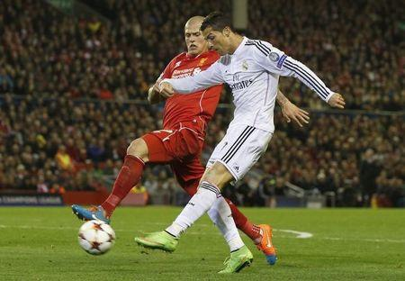 Real Madrid's Cristiano Ronaldo shoots past Liverpool's Martin Skrtel during their Champions League Group B soccer match at Anfield in Liverpool