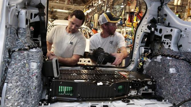 Ford Motor assembly workers install the battery pack in the rear of a 2013 Ford C-MAX Hybrid vehicle at the Michigan Assembly Plant in Wayne