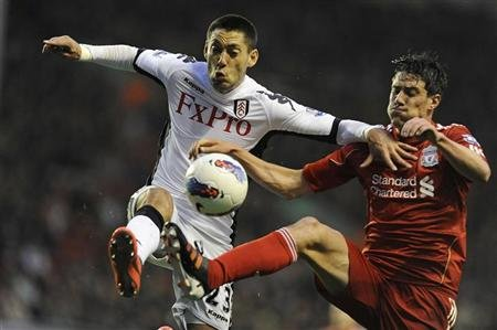 Fulham's Dempsey challenges Liverpool's Kelly during their English Premier League soccer match in Liverpool