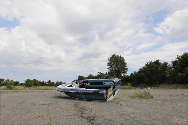 In a July 31, 2012 photo, a boat is dumped in a field in east Detroit. Abandoned lots, alleys and neglected parks in Detroit used to be a favorite destination for discarded tires and trash. But over t
