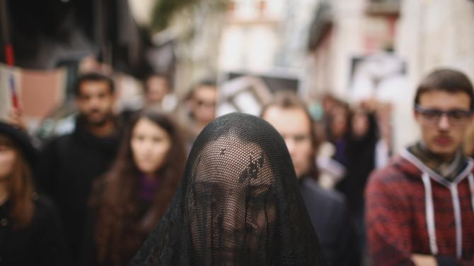A woman wearing a veil walks during a mock funeral march to protest against the condition of a school's building in Lisbon