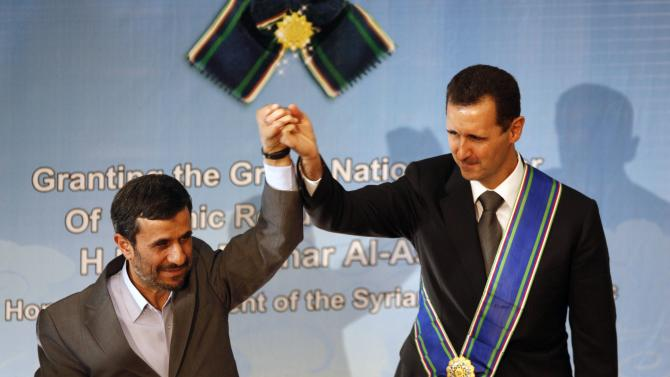 FILE - In this Oct. 2, 2010 file photo, Iranian President Mahmoud Ahmadinejad, left, holds up the hand of his Syrian counterpart Bashar Assad after he awarded Iran's highest national medal to Assad, in a ceremony in Tehran, Iran. With even his most powerful ally, Russia, losing faith in him, President Bashar Assad may appear to be heading for a last stand against rebel forces who have been waging a ferocious battle to overthrow him for nearly two years. But Assad still has thousands of elite and loyal troops behind him, and analysts say that even if he wanted to give up the fight, it's unclear those around him would let him abandon ship and leave them to an uncertain fate.(AP Photo/Vahid Salemi, File)