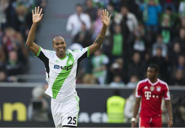 Wolfsburg's Naldo of Brazil, left, celebrates scoring his side's first goal s Bayern's David Alaba of Austria looks on during the German Bundesliga soccer match between VfL Wolfsburg and B