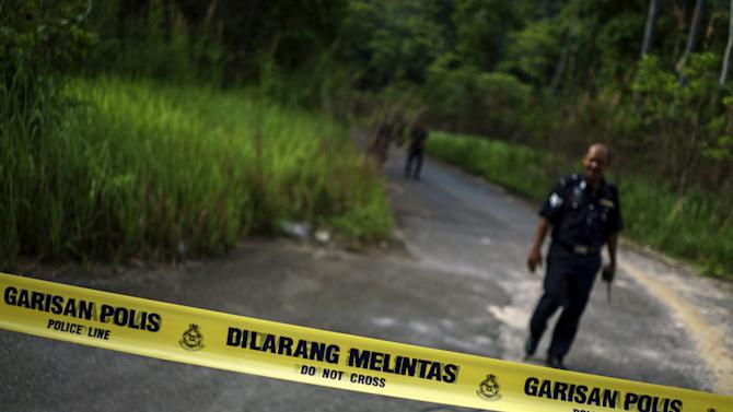 A Malaysian policeman leaves the site of the place where human remains were found, near an abandoned human trafficking camp, in the jungle close to the Thailand border at Bukit Wang Burma in northern Malaysia