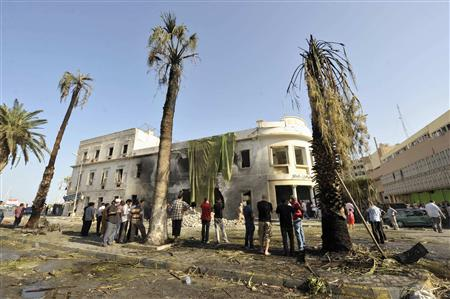 People stand near a Libyan Foreign Ministry building in Benghazi after an explosion in Benghazi