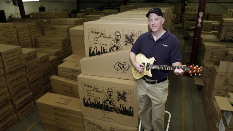 In this photo made Tuesday, April 30, 2013, Kurt Zentmaier poses in his warehouse full of  guitars in Claremont, N.H. Zentmaier is president of Rondo Music which sells its guitars online only and doesn't want an Internet sales tax. (AP Photo/Jim Cole)