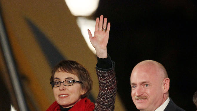 FILE - Rep. Gabrielle Giffords, left, and her husband, former astronaut Mark Kelly, wave at the start of a memorial vigil remembering the victims and survivors one year after the Arizona congresswoman was wounded in a shooting that killed six others, in this Jan. 8, 2012 file photo taken in Tucson, Ariz. Among those testifying Wednesday Jan. 30, 2013 at the year's first Senate hearing on what lawmakers should do to curb gun violence, will be Mark Kelly, husband of Giffords and a retired astronaut. Giffords, an Arizona Democrat, received a severe head wound in a 2011 shooting as she met with constituents outside a Tucson supermarket. Six people were killed and 12 others wounded.  (AP Photo/Matt York, File)