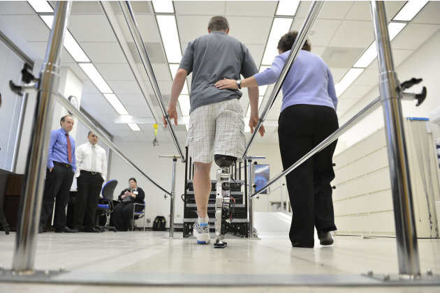 "Physical therapist assistant Suzanne Finucane, right, helps Zac Vawter as he practices walking with an experimental ""bionic"" leg at the Rehabilitation Institute of Chicago, Thursday, Oct. 25, 2012 in"