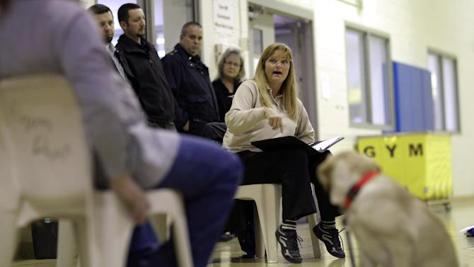 In this Dec. 18, 2012 photo, Kathy Levick, center, directs a training session with inmates and veteran assistance dogs in training as officials look on at Western Correctional Institution in Cresaptown, Md. Levick visits the maximum-security prison once a week for two hours of instruction. Otherwise, the inmates - model prisoners housed in a tier of cells reserved for the most trusted inmates - work with the dogs constantly. The dogs sleep in cages inside the inmates' 6-by-9-foot cells and accompany them to meals and activities. (AP Photo/Patrick Semansky)