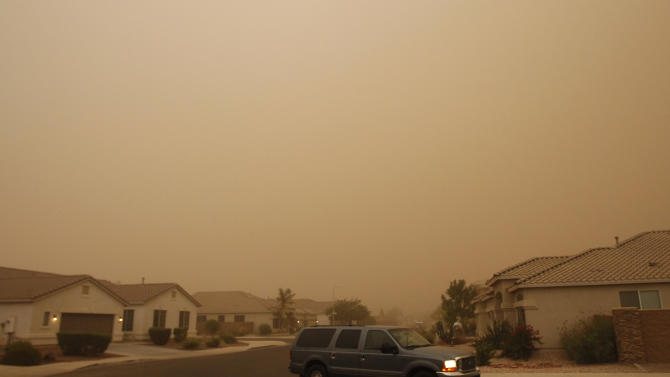 A vehicle drives through a brown cloud of blowing sand during a dust storm Monday, July 18, 2011, in Phoenix. The dust wall was about 3,000 feet high and created winds of 25 to 30 mph, with gusts of up to 40 mph, said Austin Jamison, a meteorologist with the National Weather Service. Visibility was down to less than a quarter-mile in some areas, he said.  (AP Photo/Ross D. Franklin)