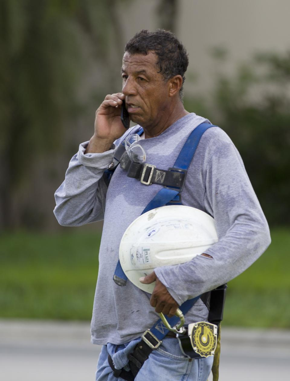 A construction worker talks on a cell phone after a section of a parking garage under construction at a Miami-Dade College campus collapsed, Wednesday, Oct. 10, 2012 in Doral, Fla., killing one worker and trapping at least two others in the rubble, officials said. (AP Photo/J Pat Carter)