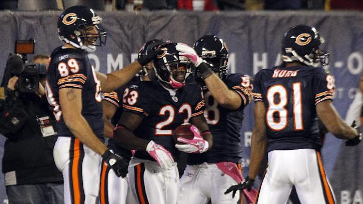 Chicago Bears' Devin Hester (23) is congratulated by teammates after his 98-yard kickoff return against the Minnesota Vikings in the second half of an NFL football game, Sunday, Oct. 16, 2011, in Chicago. (AP Photo/Charles Rex Arbogast)