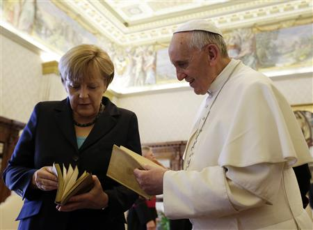 Pope Francis exchanges gifts with German Chancellor Angela Merkel during a private audience at the Vatican