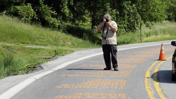 Thurmont, Md. Town Commissioner Tom Kinniard takes photos Wednesday, May, 16, 2012 of messages spray painted on Route 77, the road leading to Catoctin Park, where Camp David is and where this weekend's G8 Summit will be held. Washington-based group ONE, a group that raises public awareness of worldwide poverty, spray painted hundreds of short messages on state Route 77 near Thurmont.  (AP Photo/Timothy Jacobsen)