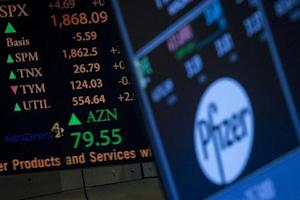 The ticker symbol for AstraZeneca is displayed next to a ticker for Pfizer on the floor of the New York Stock Exchange