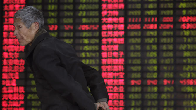 An investor walks past the stock price monitor at a private securities company on Monday March 4, 2013 in Shanghai, China. Uncertainty about the outcome of a budget battle in Washington pushed Asian stock markets lower on Monday. (AP Photo/Eugene Hoshiko)