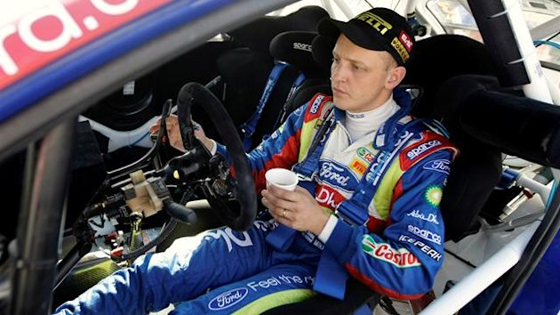 Ford team driver Mikko Hirvonen of Finland has a drink of coffee after the ninth stage of the WRC Rally of Spain in Tarragona