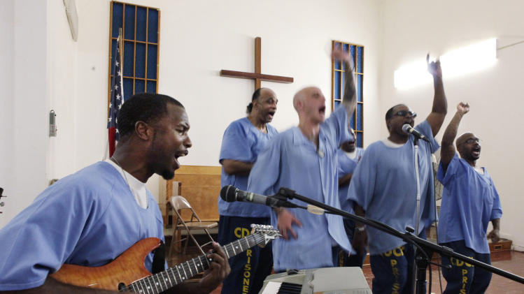 In this photo taken Thursday, Aug. 9, 2012 inmate Robert Ross, 32, far left, a leader in the seminary training program sings one of his musical compositions during a college-level seminary course held at the California Rehabilitative Center in Norco, Calif. The program, called The Urban Ministry Institute, TUMI, started as an experiment in Norco's prison four years ago and is now expanding to 18 California prisons and nearly 900 inmates, including women, thanks to a $2.1 million gift from a wealthy Malibu real estate entrepreneur. The program aims to transform inmates into church leaders, pastors, teachers and evangelists. (AP Photo/Damian Dovarganes)