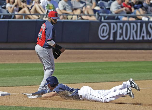San Diego Padres' Ryan Jackson (15) slides safely into third after hitting a triple as Cleveland Indians' Carlos Santana (41) watches during the fifth inning of an exhibition spring training b