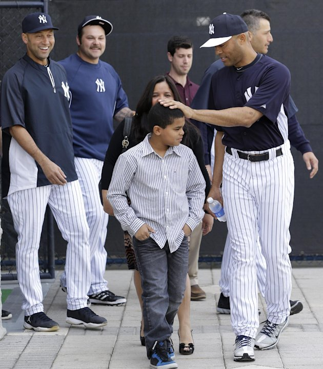 New York Yankees shortstop Derek Jeter, far left,  and reliever Joba Chamberlain, second from left, watch as pitcher Mariano Rivera, far right, pats his son Jaziel on the head before a news conference