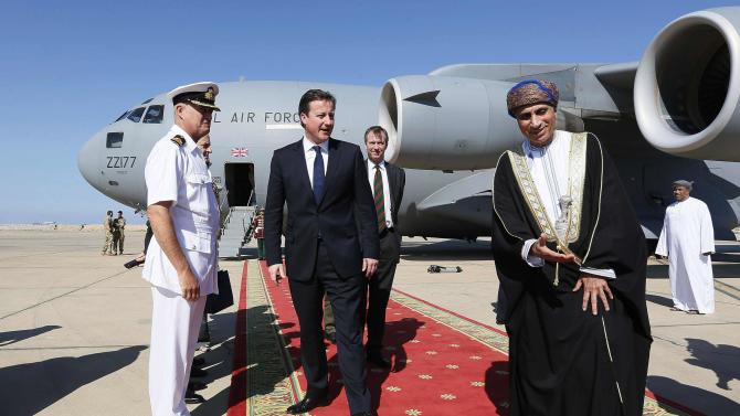 Oman's Sultan Qaboos bin Said, front right, welcomes Britain's Prime Minister David Cameron, centre, in Muscat, Oman, Friday Dec. 21, 2012. (AP Photo / Stefan Wermuth)