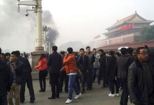 File photo of people walking along the sidewalk of Chang'an Avenue as smoke rises in front of the main entrance of the Forbidden City at Tiananmen Square in Beijing