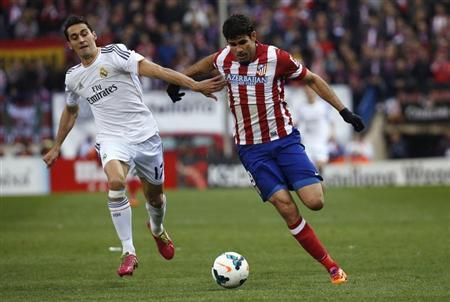 Real Madrid's Arbeloa and Atletico Madrid's Costa challenge for the ball during their Spanish first division soccer match in Madrid
