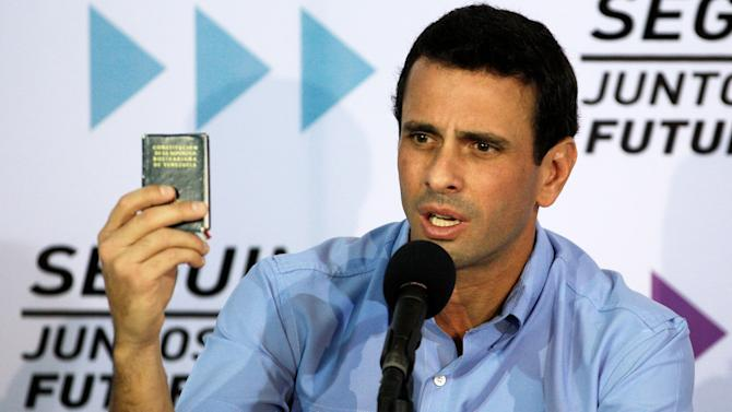 Venezuela's opposition leader Henrique Capriles holds up a miniature copy of the national constitution during a news conference in Caracas, Venezuela, Tuesday, Jan. 8, 2013. Capriles said that the Supreme Court should rule in a dispute between the opposition and President Hugo Chavez's government over whether the ailing leader's inauguration can legally be postponed. Capriles said the constitution is clear that the current presidential term ends on Jan. 10. Chavez remains in Havana after undergoing his fourth cancer surgery on Dec. 11 and hasn't spoken publicly in a month. (AP Photo/Fernando Llano)